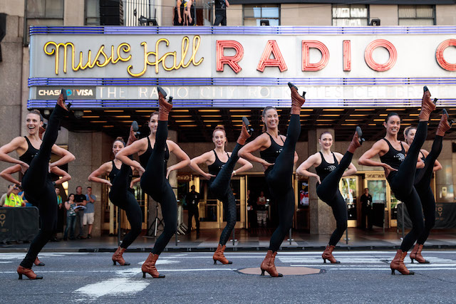 NEW YORK, NY - AUGUST 23: Members of the 'Radio City Rockettes' rehearse before their annual 'Christmas in August' event outside of Radio City Music Hall on 6th Avenue, August 23, 2016 in New York City. The Rockettes performed 'Sleigh Ride' in the street while traffic was stopped on 6th Avenue. (Photo by Drew Angerer/Getty Images)