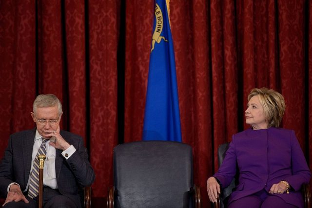 Senate Minority Leader Senator Harry Reid (D-NV) and former presidential candidate Hillary Clinton listen during a portrait unveiling for the outgoing Senator on Capitol Hill December 8, 2016 in Washington, D.C. (BRENDAN SMIALOWSKI/AFP/Getty Images)