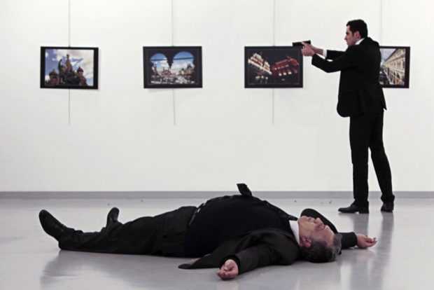"TOPSHOT - EDITORS NOTE: Graphic content / This picture taken on December 19, 2016 shows Andrei Karlov (bottom), the Russian ambassador to Ankara, lying on the floor after being shot by Mevlut Mert Altintas (R) during an attack during a public event in Ankara. A gunman crying ""Aleppo"" and ""revenge"" shot Karlov while he was visiting an art exhibition in Ankara on December 19, witnesses and media reports said. The Turkish state-run Anadolu news agency said the gunman had been ""neutralised"" in a police operation, without giving further details. HASIM KILIC/AFP/Getty Images"