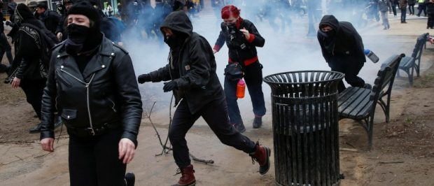 Activists race after being hit by a stun grenade while protesting against Trump on the sidelines of the inauguration. REUTERS/Adrees Latif