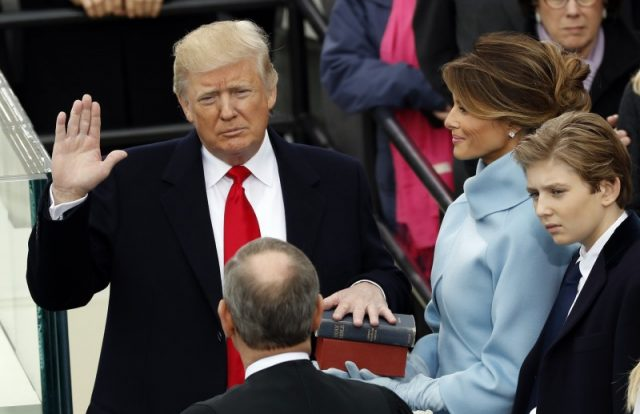 Donald Trump takes the oath of office with his wife Melania and son Barron at his side. REUTERS/Kevin Lamarque
