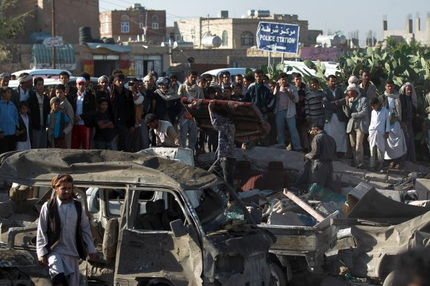 Yemenis stand at the site of a Saudi air strike against Huthi rebels near Sanaa Airport on March 26, 2015, which killed at least 13 people. Saudi warplanes bombed Huthi rebels in Yemen, launching a military intervention by a 10-nation coalition to prevent the fall of embattled President Abedrabbo Mansour Hadi. MOHAMMED HUWAIS/AFP/Getty Images