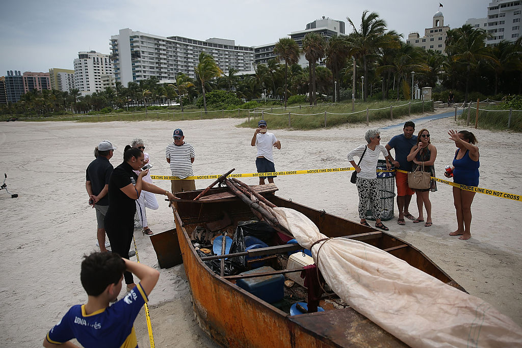 People look at a Cuban migrant boat that brought 12 people and a dog to the beach on September 15, 2015 in Miami Beach, Florida (Getty Images)