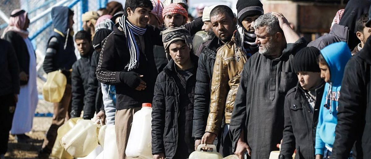 Refugees who fled the Iraqi city of Mosul due to the fighting between government forces and Islamic State (IS) group jihadists, queue for heating fuel at the UN-run al-Hol refugee camp in Syria's Hasakeh province, on January 29, 2017. / AFP / DELIL SOULEIMAN (Photo credit should read DELIL SOULEIMAN/AFP/Getty Images)