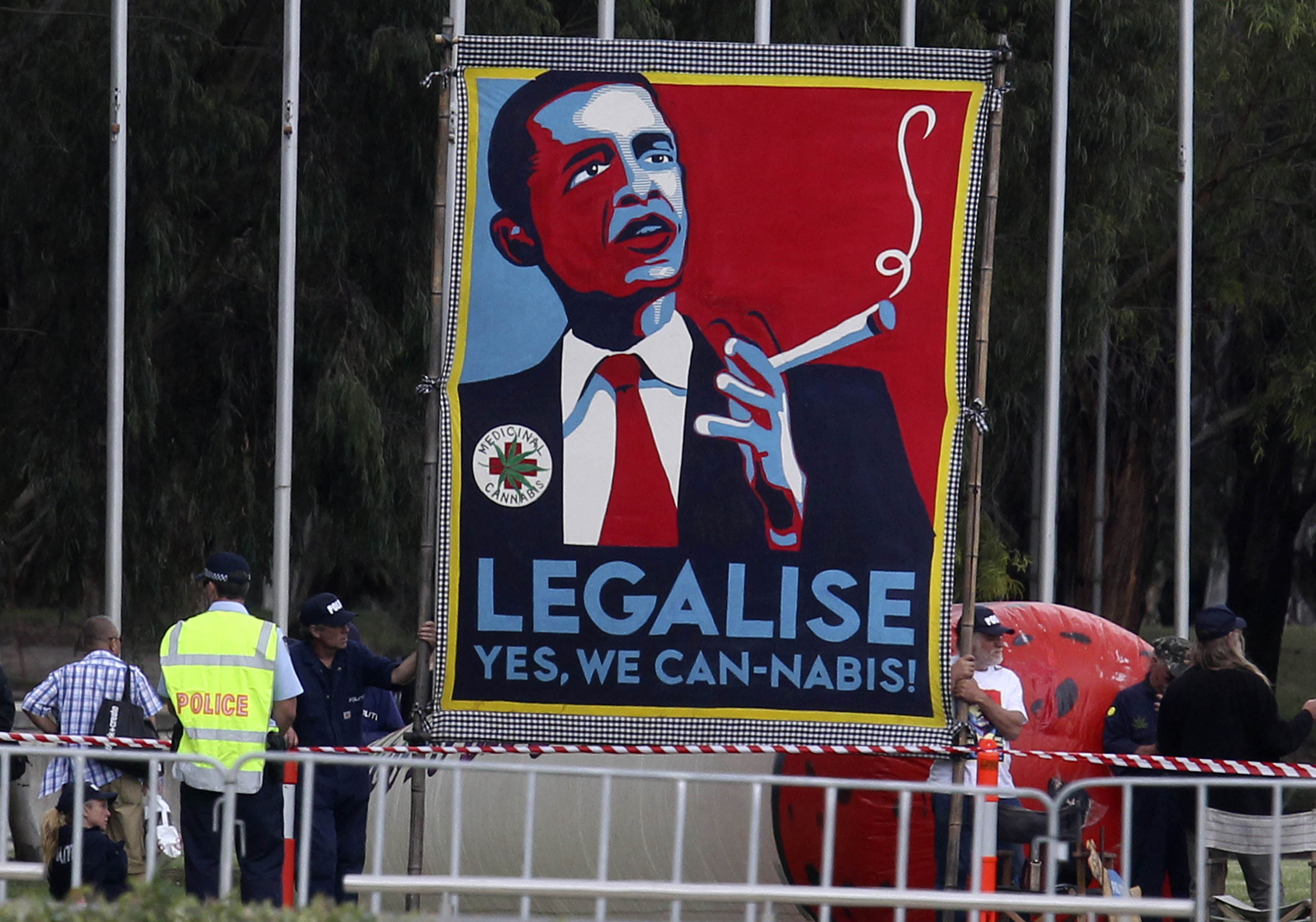 Protesters hold giant sign to legalize marijuana before U.S. President Barack Obama arrives to participate in an official arrival ceremony at Parliment House in Canberra, Australia, November 16, 2011. REUTERS/Larry Downing (AUSTRALIA - Tags: POLITICS) - RTR2U2RV