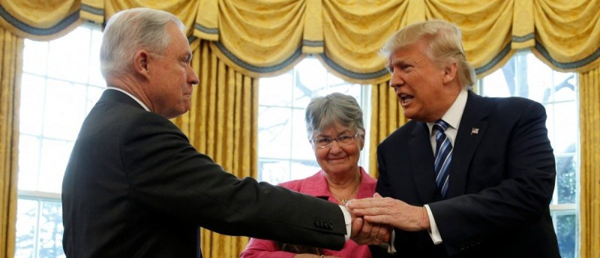 U.S. President Donald Trump congratulates Jeff Sessions after he was sworn in as U.S. Attorney General as his wife Mary Sessions looks on during a ceremony in the Oval Office of the White House in Washington, U.S., February 9, 2017. REUTERS/Kevin Lamarque