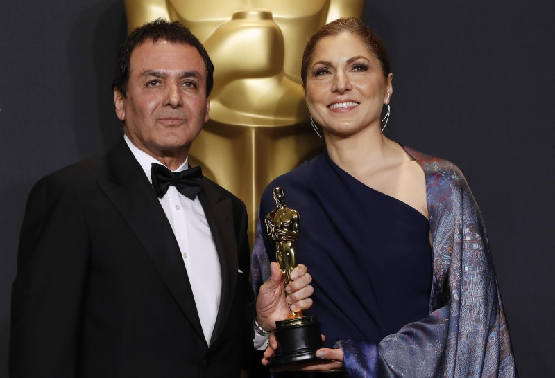 """89th Academy Awards - Oscars Backstage - Hollywood, California, U.S. - 26/02/17 - Anousheh Ansari and Firouz Naderi pose with the Oscar they accepted on behalf of Asghar Farhadi, who won the Best Foreign Language Film for """"The Salesman"""". REUTERS/Lucas Jackson"""
