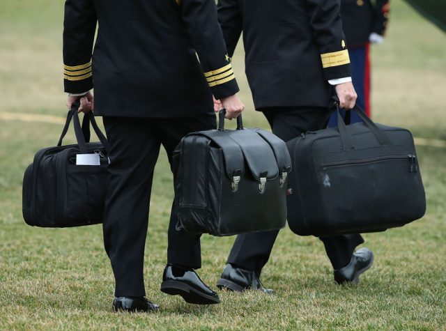Two military aides carry the nuclear football. (Photo: Mark Wilson/Getty Images)