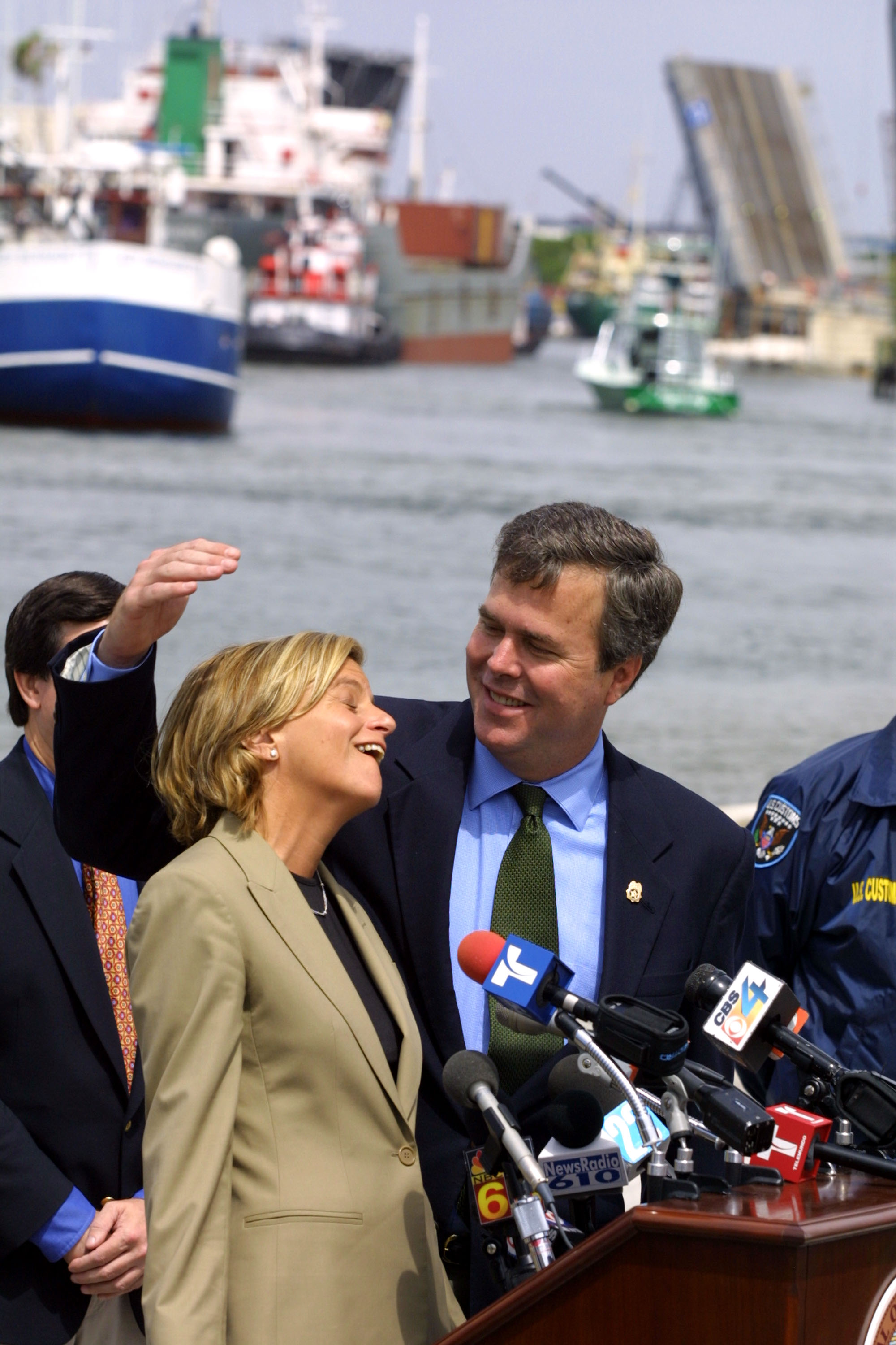 Republican Florida Congresswoman Ileana Ros-Lehtinen and Florida Governor Jeb Bush share a light moment as Ros-Lehtinen has to use a small ladder to get high enough to speak into the microphones during a press conference May 8, 2001 along the Miami River. The press conference was held to applaud the efforts of federal, state and local law enforcement for the progress being made in Operation Riverwalk in Miami, Florida. The operation is a minimum two-year law enforcement action which seeks to eliminate the drug trade on the Miami River. (Photo by Joe Raedle/Newsmakers)