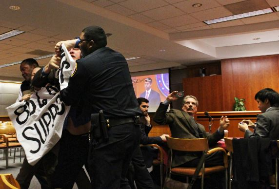Security removes radical activist, Kevin Zeese, from an FCC open meeting in 2014 (Popular Resistance)