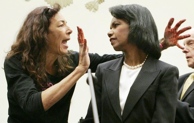 "Desiree Fairooz of Texas, 50, jumps up in front of U.S. Secretary of State Condoleezza Rice before Rice testifies before the House Foreign Affairs Committee on Capitol Hill in Washington October 24, 2007. Fairooz, an anti-war protester waved blood-colored hands in Rice's face at a congressional hearing on Wednesday and shouted ""war criminal!"", but was pushed away and detained by police. At right is the committee Chairman Rep. Tom Lantos (D-CA). (Photo:REUTERS/Larry Downing)"