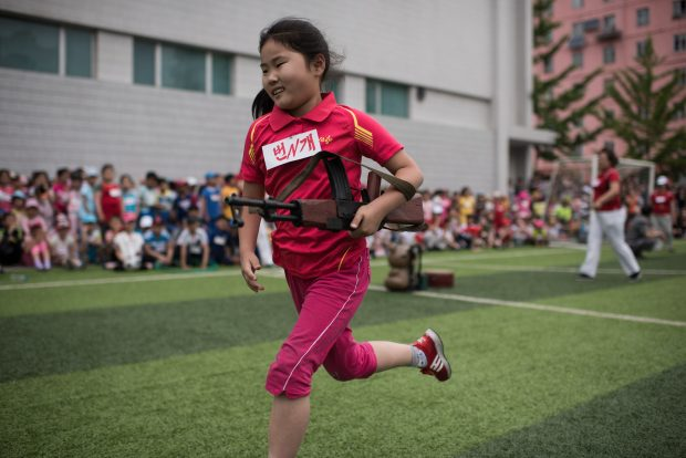 A girl carrying a mock rifle completes an obstacle course as school children take part in sports games marking 'Children's Union Foundation day', in Pyongyang on June 6, 2017. (ED JONES/AFP/Getty Images)