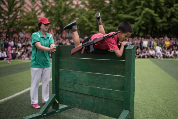 A boy carrying a mock rifle completes an obstacle course as school children take part in sports games marking 'Children's Union Foundation day', in Pyongyang on June 6, 2017. (ED JONES/AFP/Getty Images)