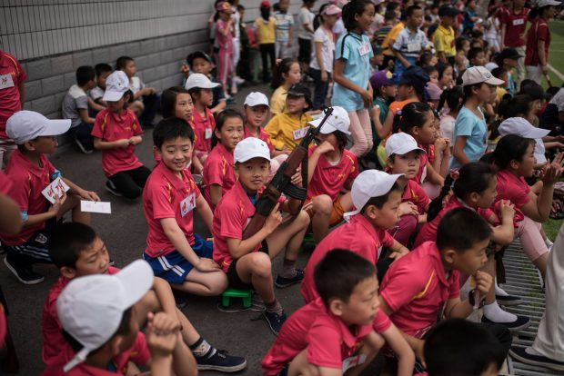 A boy holds a mock rifle as he sits with others to take part in sports games marking 'Children's Union Foundation day', in Pyongyang on June 6, 2017. (ED JONES/AFP/Getty Images)