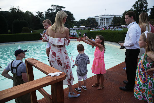 WASHINGTON, DC - JUNE 22: Ivanka Trump (2nd L), daughter and assistant to President Donald Trump, and her children, daughter Arabella Rose Kushner (R), sons Joseph Frederick Kushner (3rd L) and Theodore James Kushner (L) watch remote control toy sail boats in the fountain at the South Lawn during a Congressional Picnic at the White House June 22, 2017 in Washington, DC. President Trump and the first lady hosted their first Congressional Picnic with the theme, Picnic in the Park, which is modeled after a summer evening in Central Park in New York. (Photo by Alex Wong/Getty Images)