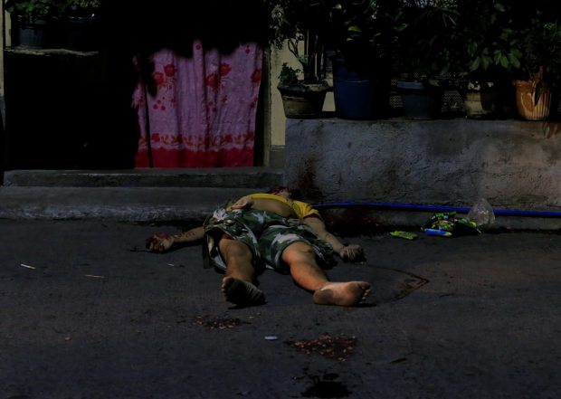 The body of a suspected drug pusher, whom police investigators said was shot and killed by unidentified men, lies along a street in Quezon city, metro Manila, Philippines March 1, 2017. REUTERS/Romeo Ranoco