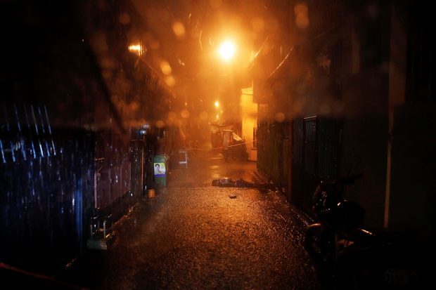 Heavy rain pours as the body of a man killed by unidentified gunmen riding motorcycles is left in a narrow alley in Manila, Philippines early October 11, 2016. REUTERS/Damir Sagolj