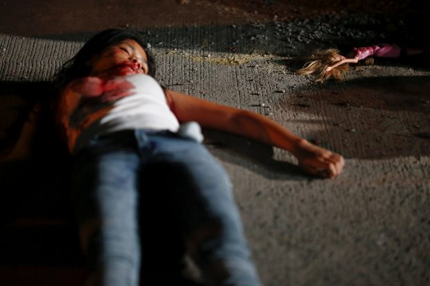 "A 17 year old girl lays dead next to her doll after she and her friend were killed by unknown motorcycle-riding gunmen, in an alley in Manila, Philippines early October 26, 2016. According to the police, a sign on a cardboard reading ""Tulak ka, hayop ka"", which translates to ""You are a (drug) pusher, you are an animal"" was found with the body of girl's friend. REUTERS/Damir Sagolj"