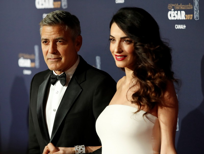 FILE PHOTO: Actor George Clooney and his wife Amal pose as they arrive at the 42nd Cesar Awards ceremony in Paris, France, February 24, 2017. REUTERS/Gonzalo Fuentes/File Photo