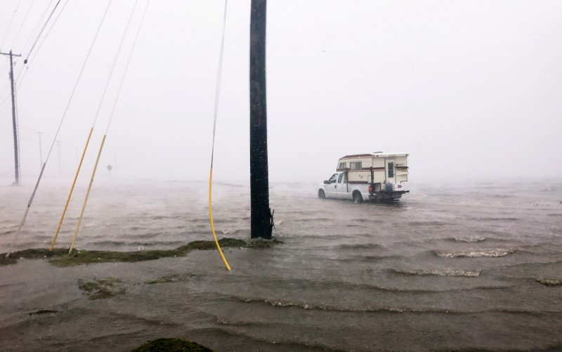 """Craig """"Cajun"""" Uggen, 57, nearly floods his truck as Hurricane Harvey comes ashore in Corpus Christi, Texas. Minutes later, high winds blew off the camper carrying all of his belongings. REUTERS/Brian Thevenot"""