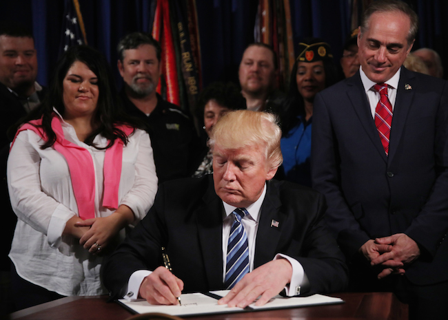President Donald Trump signs an Executive Order on improving accountability and whistle-blower protection at the Veterans Affairs Department in Washington, April 27, 2017. REUTERS/Carlos Barria