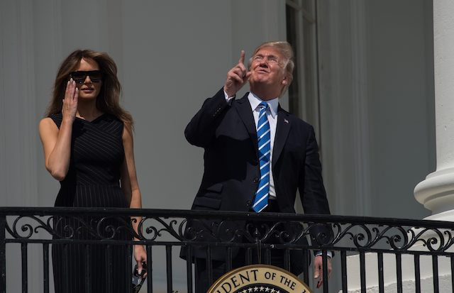 US President Donald Trump looks up a the partial solar eclipse with First Lady Melania Trump from the balcony of the White House in Washington, DC, on August 21, 2017. The Great American Eclipse completed its journey across the United States Monday, with the path of totality stretching coast-to-coast for the first time in nearly a century. / AFP PHOTO / NICHOLAS KAMM (Photo credit should read NICHOLAS KAMM/AFP/Getty Images)