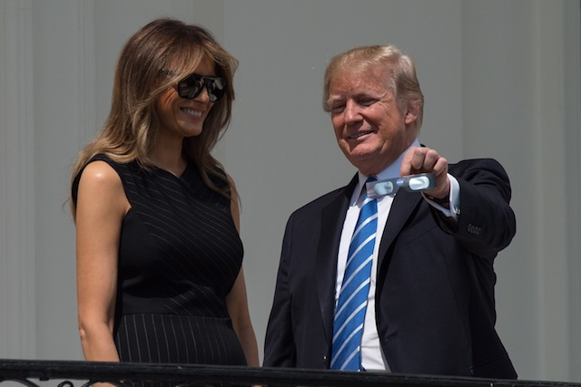 US President Donald Trump shows his eclipse glasses First Lady Melania Trump from the balcony of the White House during the partial solar eclipse in Washington, DC, on August 21, 2017. The Great American Eclipse completed its journey across the United States Monday, with the path of totality stretching coast-to-coast for the first time in nearly a century. / AFP PHOTO / NICHOLAS KAMM (Photo credit should read NICHOLAS KAMM/AFP/Getty Images)