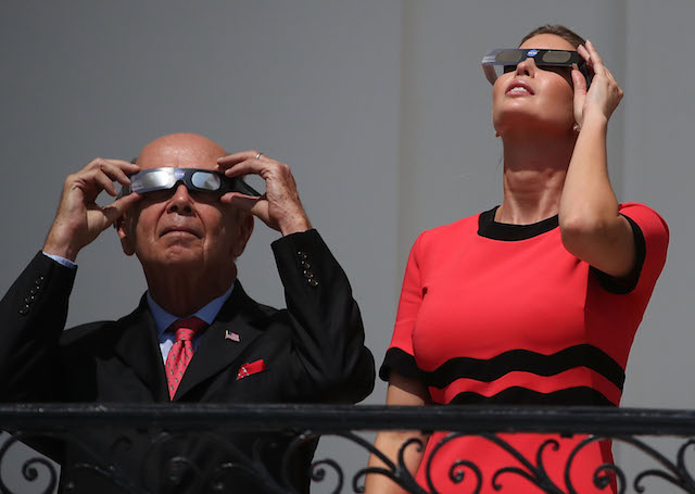 """WASHINGTON, DC - AUGUST 21: (AFP OUT) Ivanka Trump and Commerce Secretary Wilbur Ross wear special glasses to look up at the Solar Eclipse, at the White House on August 21, 2017 in Washington, DC. Millions of people have flocked to areas of the U.S. that are in the """"path of totality"""" in order to experience a total solar eclipse. (Photo by Mark Wilson/Getty Images)"""