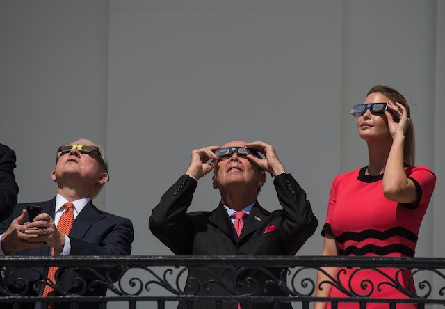 Ivanka Trump (R), daughter and advisor of US President Donald Trump, Commerce Secretary Wilbur Ross (C) and Attorney General Jeff Sessions look up at the partial solar eclipse from the balcony of the White House in Washington, DC, on August 21, 2017. / AFP PHOTO / NICHOLAS KAMM (Photo credit should read NICHOLAS KAMM/AFP/Getty Images)