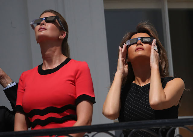 """WASHINGTON, DC - AUGUST 21: First lady Melania Trump (R) and Ivanka Trump wear special glasses to view the solar eclipse at the White House on August 21, 2017 in Washington, DC. Millions of people have flocked to areas of the U.S. that are in the """"path of totality"""" in order to experience a total solar eclipse. (Photo by Mark Wilson/Getty Images)"""