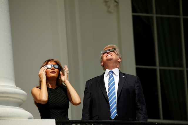 U.S. President Donald Trump watches the solar eclipse with first Lady Melania Trump from the Truman Balcony at the White House in Washington, U.S., August 21, 2017. REUTERS/Kevin Lamarque - RTS1CPBD