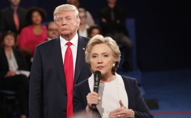Trump listens as Clinton answers a question from the audience during their presidential town hall debate in St. Louis, October 9, 2016. REUTERS/Rick Wilking