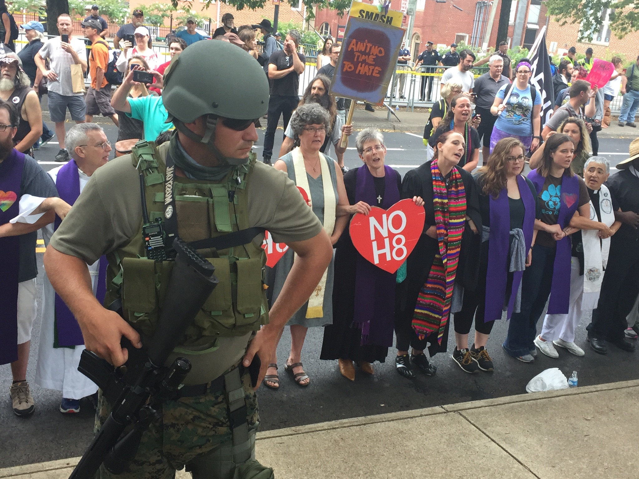 """A state militia member watches as faith leaders sing """"this little light of mine"""" over his shoulder. (Henry Rodgers, TheDCNF)"""