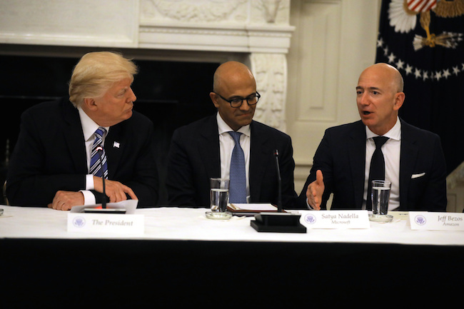 President Donald Trump and Satya Nadella, CEO of Microsoft Corporation listen as Jeff Bezos, CEO of Amazon speaks during an American Technology Council roundtable at the White House in Washington, June 19, 2017. REUTERS/Carlos Barria