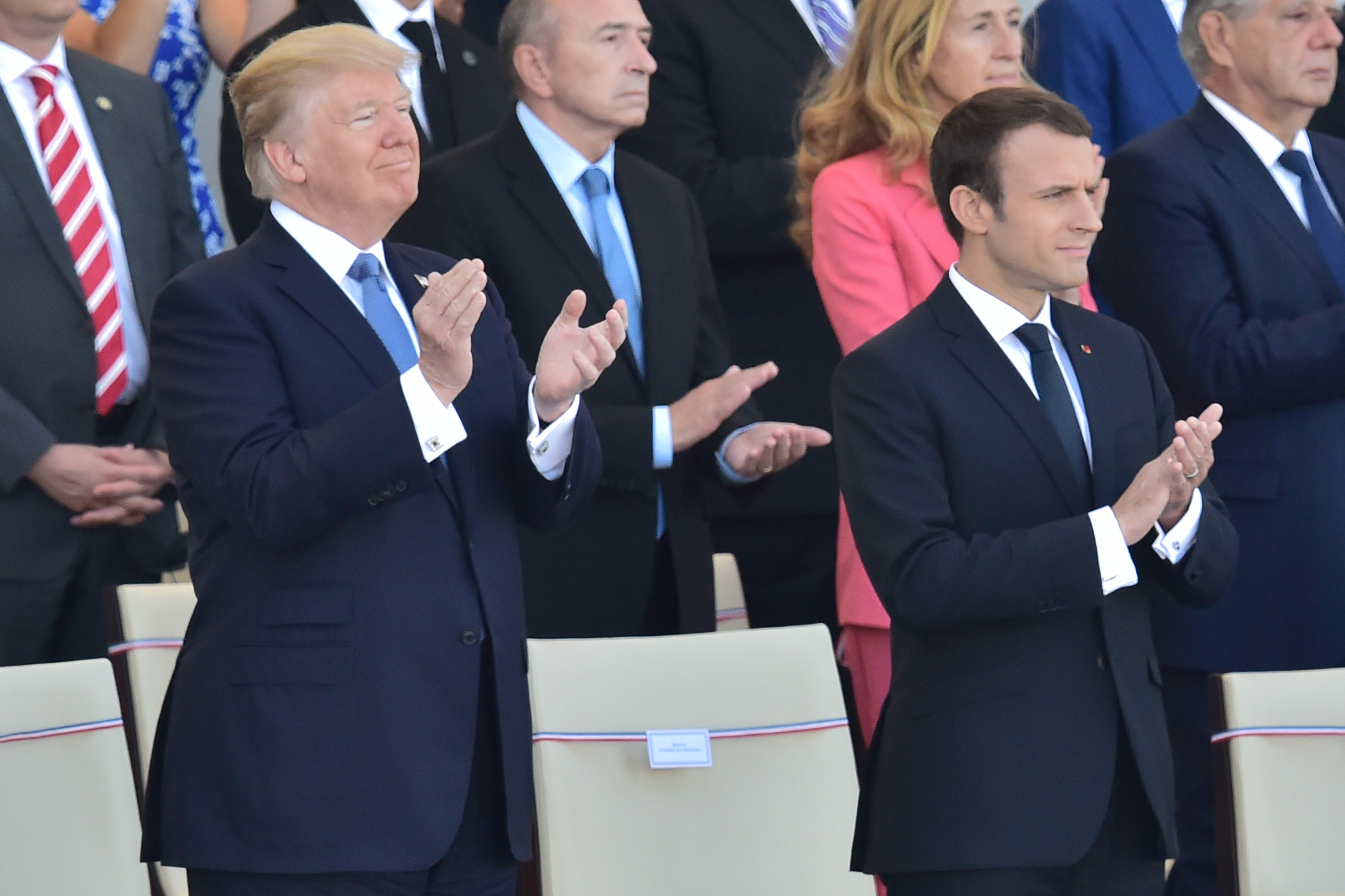 US President Donald Trump (L) and his French counterpart Emmanuel Macron applaud as they watch the annual Bastille Day military parade on the Champs-Elysees avenue in Paris on July 14, 2017. The parade on Paris's Champs-Elysees will commemorate the centenary of the US entering WWI and will feature horses, helicopters, planes and troops. CHRISTOPHE ARCHAMBAULT/AFP/Getty Images
