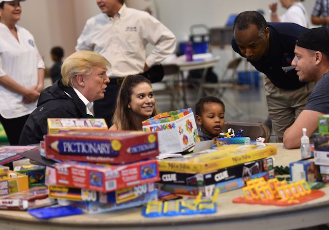 US President Donald Trump, with Secretary of Housing and Urban Development Ben Carson (2nd R), visits Hurricane Harvey victims at NRG Center in Houston on September 2, 2017. US President Donald Trump, with visits Hurricane Harvey victims at NRG Center in Houston on September 2, 2017. / AFP PHOTO / Nicholas Kamm (Photo credit should read NICHOLAS KAMM/AFP/Getty Images)
