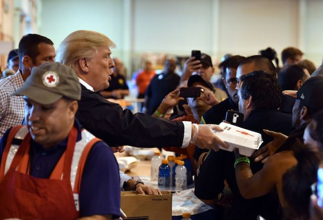 US President Donald Trump serves food to Hurricane Harvey victims at NRG Center in Houston on September 2, 2017. / AFP PHOTO / Nicholas Kamm (Photo credit should read NICHOLAS KAMM/AFP/Getty Images)