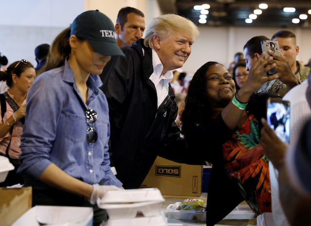 U.S. President Donald Trump poses for a photo as he and first lady Melania Trump help volunteers hand out meals during a visit with flood survivors of Hurricane Harvey at a relief center in Houston, Texas, U.S., September 2, 2017. REUTERS/Kevin Lamarque - RC1D123791F0