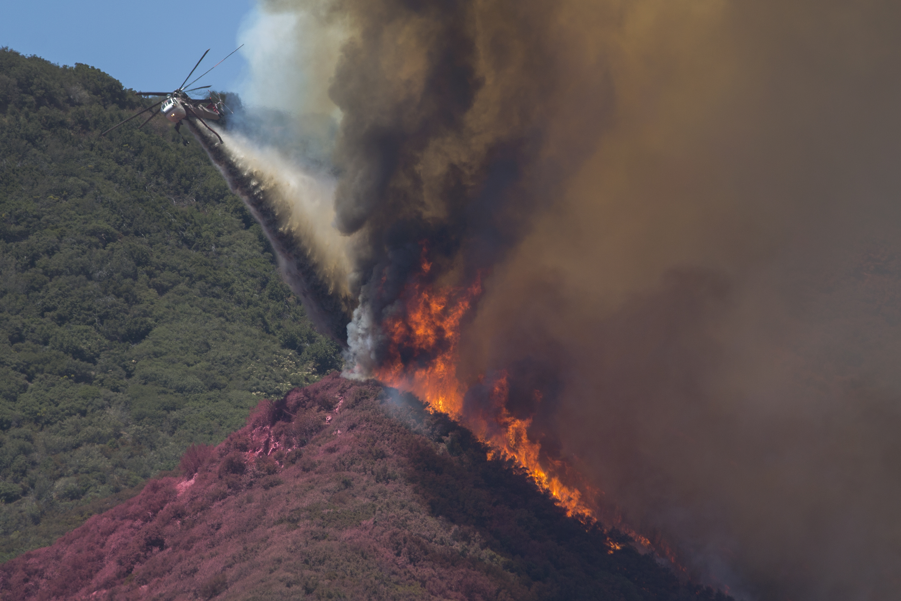 WRIGHTWOOD, CA - AUGUST 18: A firefighting helicopter pilot tries to stop flames close to jumping a ridge, even though the ridge is already painted red with fire retardant, above Cajon Boulevard at the Blue Cut Fire on August 18, 2016 near Wrightwood, California. (Photo by David McNew/Getty Images)