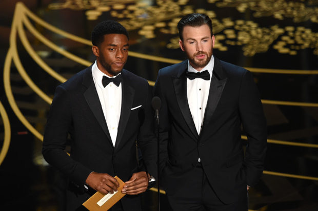HOLLYWOOD, CA - FEBRUARY 28: Actors Chadwick Boseman (L) and Chris Evans speak onstage during the 88th Annual Academy Awards at the Dolby Theatre on February 28, 2016 in Hollywood, California. (Photo by Kevin Winter/Getty Images)