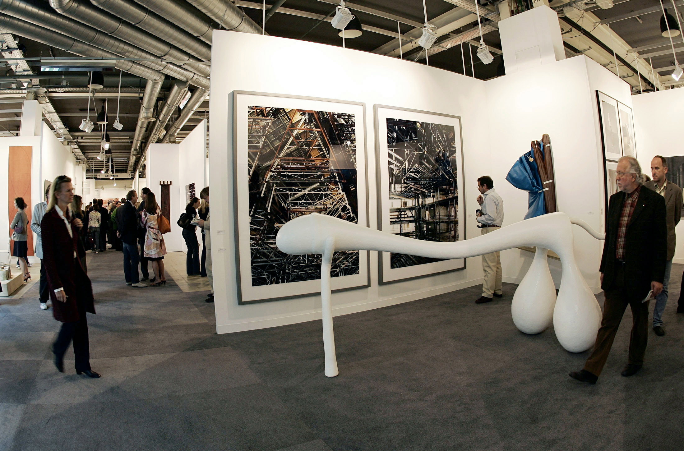 "Visitors walk by a piece of art called ""Penis Number 26"" by the Dutch Atelier van Lieshout at the 36th Art in Basel, Switzerland, June 14, 2005. Getty Images - Stringer"
