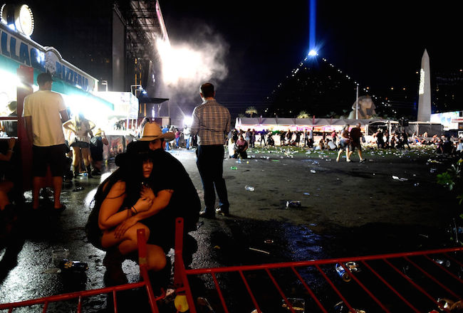 People take cover at the Route 91 Harvest country music festival after apparent gun fire was heard on October 1, 2017 in Las Vegas. (Photo by David Becker/Getty Images)