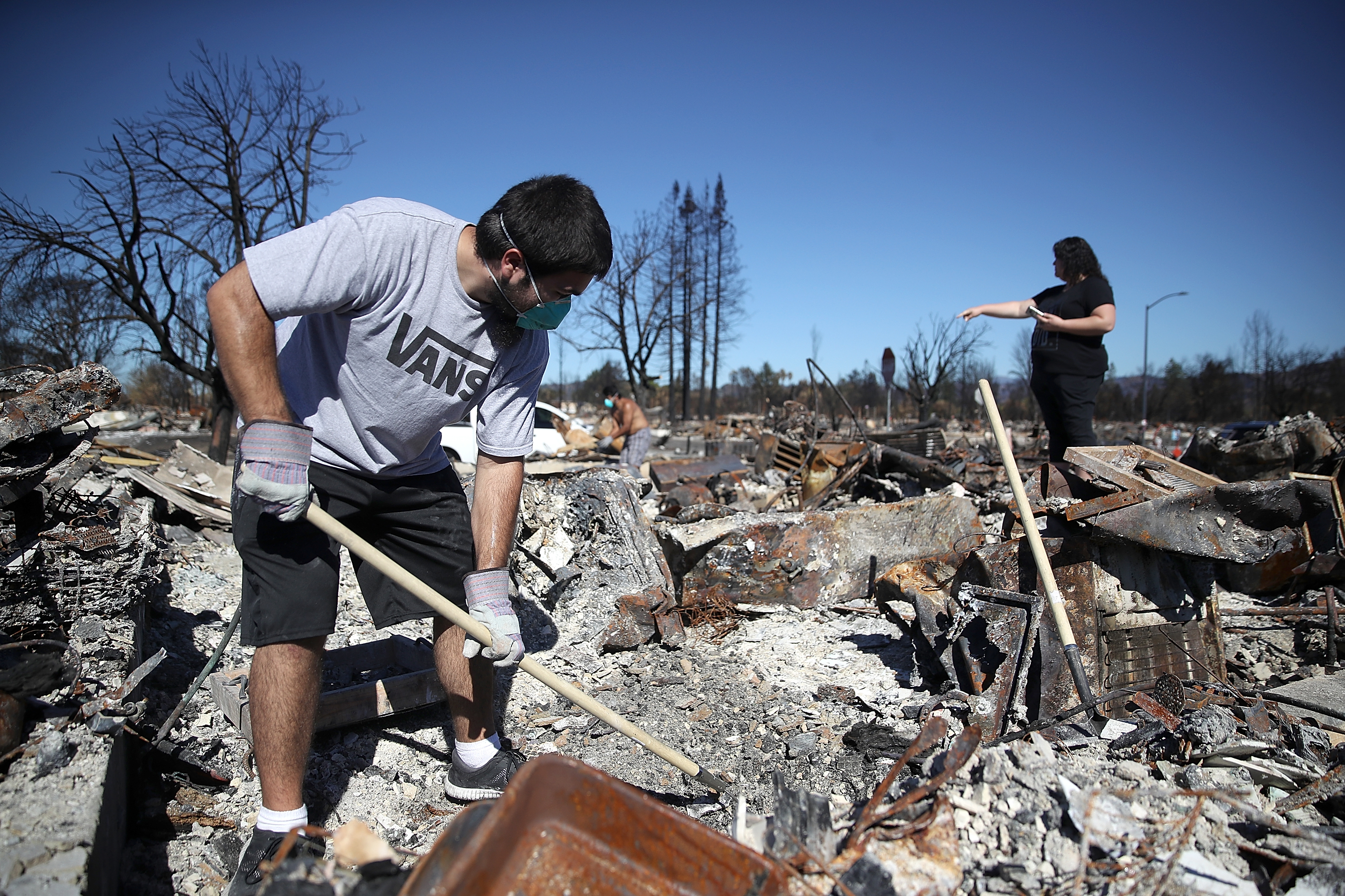 SANTA ROSA, CA - OCTOBER 23: Ben Hernandez Jr. (L) sifts through the remains of his Coffey Park home that was destroyed by the Tubbs Fire on October 23, 2017 in Santa Rosa, California. Residents are returning to their homes after a fast moving and deadly widlfire destroyed 8,400 structures and claimed the lives of at least 42 people. (Photo by Justin Sullivan/Getty Images)