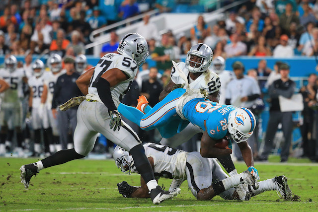 MIAMI GARDENS, FL - NOVEMBER 05: running back Damien Williams #26 of the Miami Dolphins is tackled by outside linebacker Cory James #57, middle linebacker NaVorro Bowman #53 of the Oakland Raiders and middle linebacker NaVorro Bowman #53 of the Oakland Raiders of the Oakland Raiders, at Hard Rock Stadium on November 5, 2017 in Miami Gardens, Florida. (Photo by Chris Trotman/Getty Images)