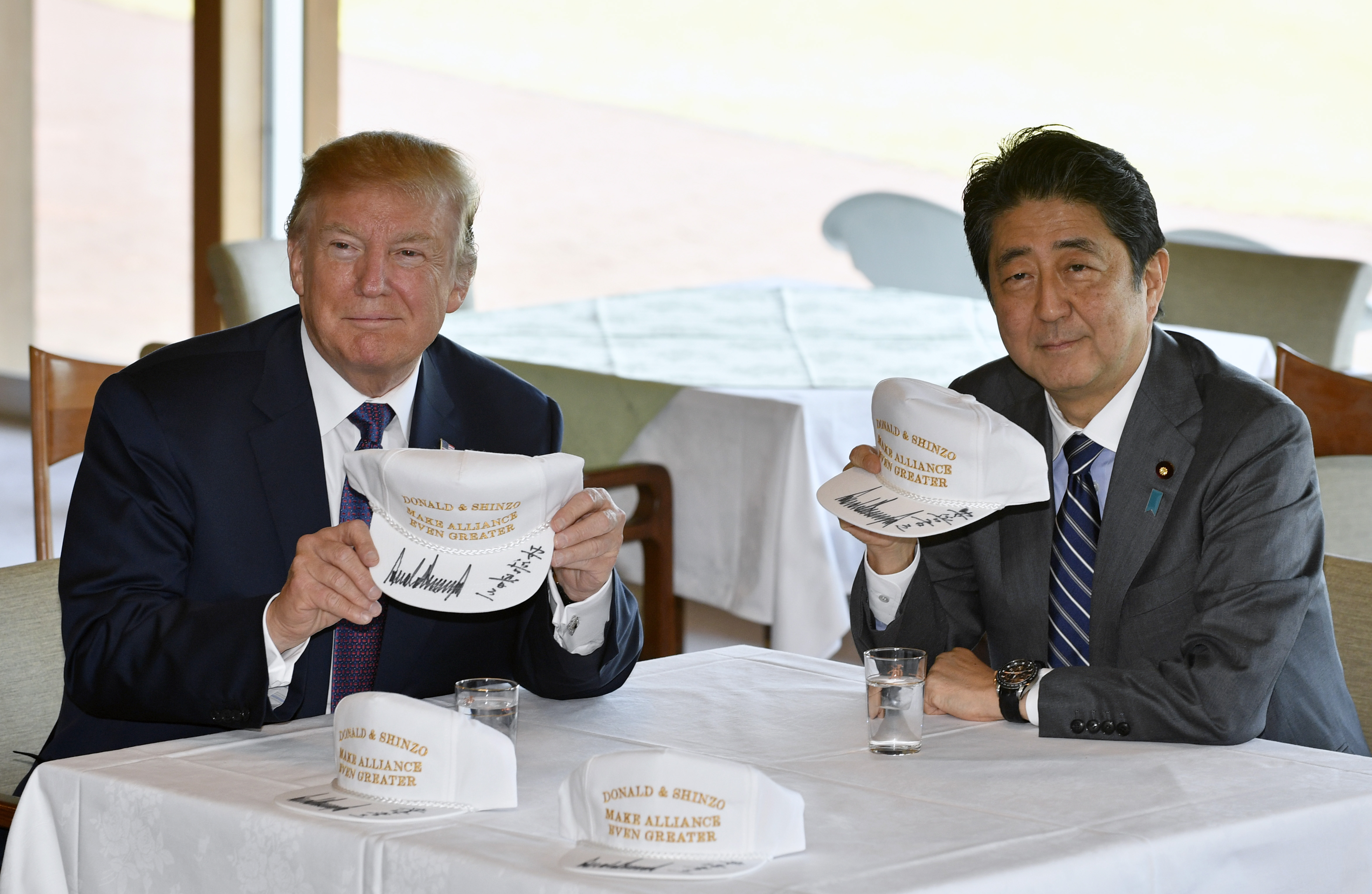 US President Donald Trump (L) and Japanese Prime Minister Shinzo Abe pose after they signed hats reading 'Donald and Shinzo, Make Alliance Even Greater' at the Kasumigaseki Country Club in Kawagoe, near Tokyo on November 5, 2017. Trump touched down in Japan, kicking off the first leg of a high-stakes Asia tour set to be dominated by soaring tensions with nuclear-armed North Korea. FRANCK ROBICHON/AFP/Getty Images