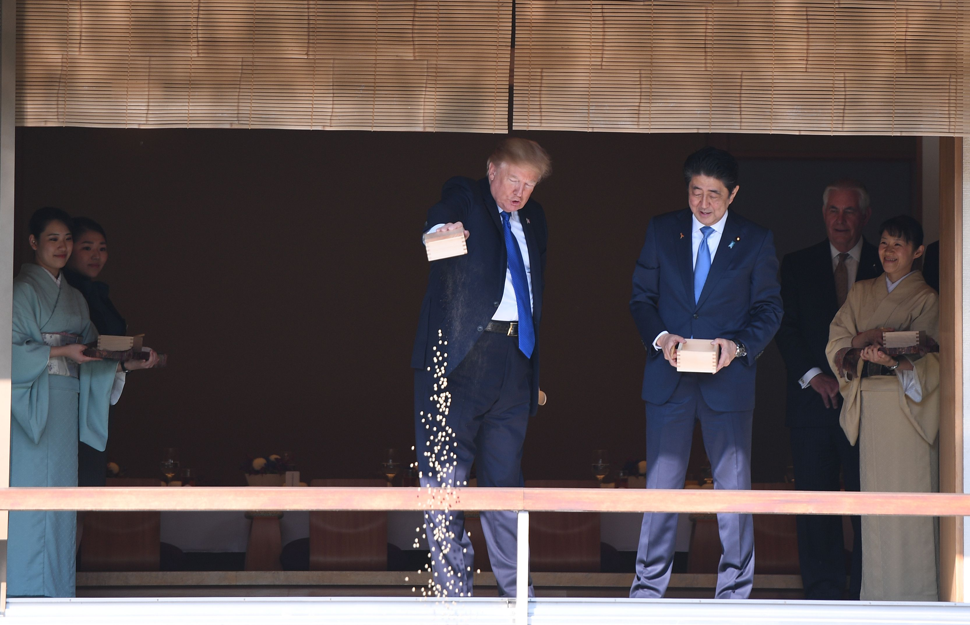 """TOPSHOT - US President Donald Trump (C) feeds koi fish as Japanese Prime Minister Shinzo Abe (R)looks on during a welcoming ceremony in Tokyo on November 6, 2017. Trump lashed out at the US trade relationship with Japan, saying it was """"not fair and open"""", as he prepared for formal talks with his Japanese counterpart. JIM WATSON/AFP/Getty Images"""