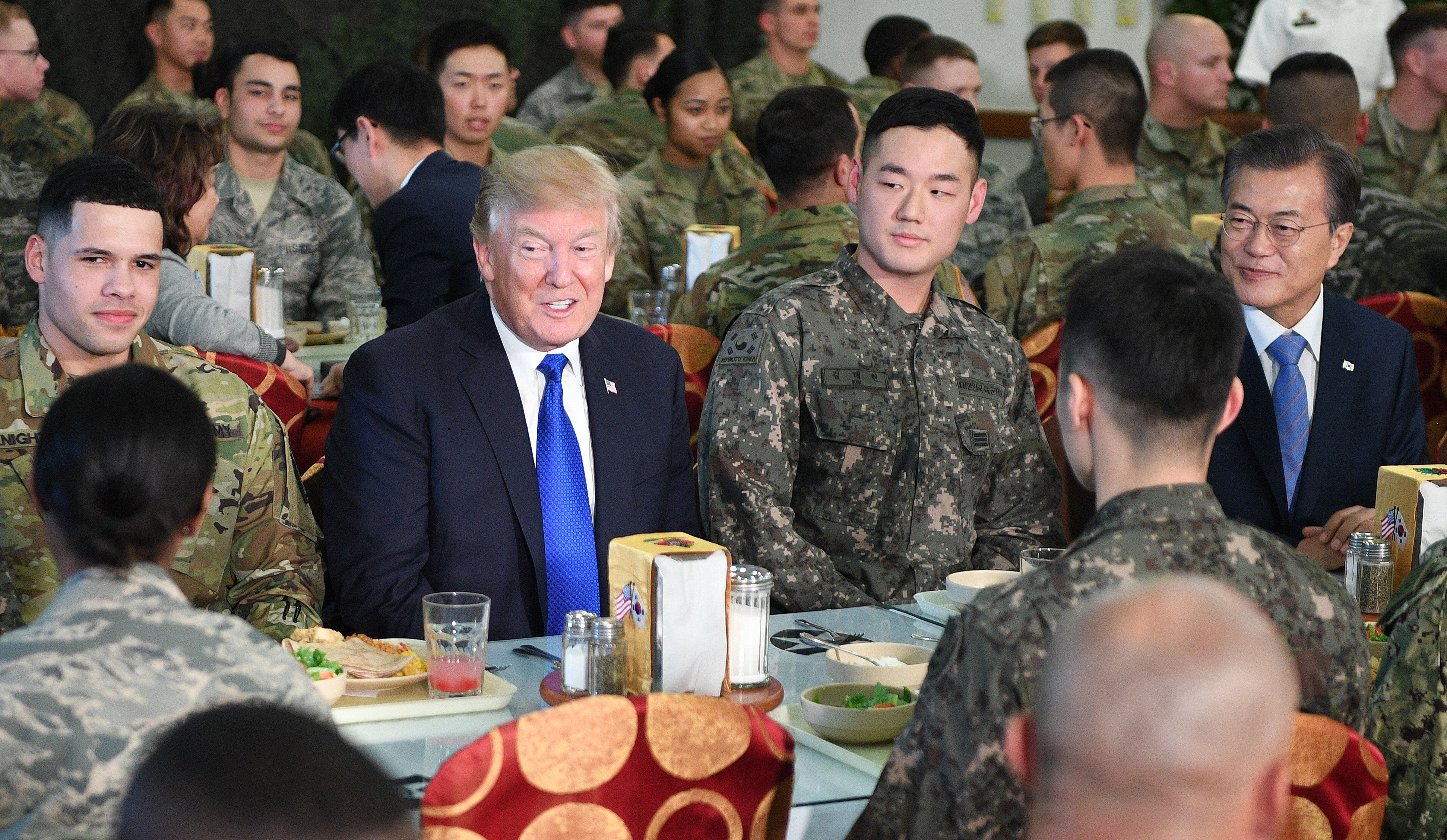 US President Donald Trump (2nd-L) talks to military personnel while South Korean President Moon Jae-In (R) looks on at Camp Humphreys in Pyeongtaek, south of Seoul on November 7, 2017. Trump's marathon Asia tour moves to South Korea, another key ally in the struggle with nuclear-armed North Korea, but one with deep reservations about the US president's strategy for dealing with the crisis. JIM WATSON/AFP/Getty Images