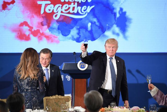 "US President Donald Trump (R) holds a glass as South Korea's President Moon Jae-In (C) talks to First Lady Melania Trump during a state dinner at the presidential Blue House in Seoul on November 7, 2017. North Korea poses a worldwide threat that requires worldwide action, President Donald Trump said in Seoul on November 7, but insisted ""we are making a lot of progress"" in reining in the rogue state. / AFP PHOTO / Jim WATSON (Photo credit should read JIM WATSON/AFP/Getty Images)"