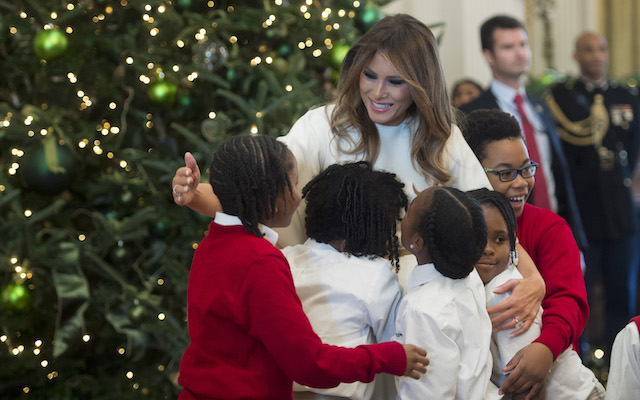 US First Lady Melania Trump hugs children in the East Room as she tours Christmas decorations at the White House in Washington, DC, November 27, 2017. / AFP PHOTO / SAUL LOEB (Photo credit should read SAUL LOEB/AFP/Getty Images)
