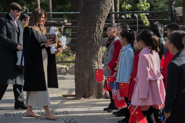 US First Lady Melania Trump (2nd L) offers stuffed toy eagles, from the US, to children at the Beijing Zoo in Beijing on November 10, 2017. / AFP PHOTO / NICOLAS ASFOURI (Photo credit should read NICOLAS ASFOURI/AFP/Getty Images)